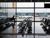 Un passager seul vu en silhouette attendant dans l'aéroport de Francfort Photographie stock libre de droits
