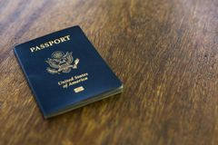 Un passaporto americano blu sopra uno scrittorio di legno Immagine Stock Libera da Diritti