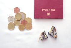Un passaporto, monete e stivali su un fondo bianco cose essenziali per un auto-stop fotografie stock