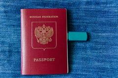 Un passaporto russo per il viaggio all'estero con il disco su un fondo blu Fotografie Stock