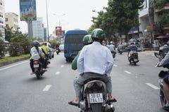 Un passeggero utilizza i servizi del moto-taxi della gru a benna in una via di Ho Chi Minh City fotografia stock libera da diritti