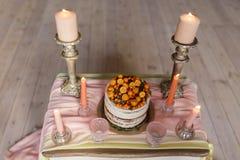 Un pastel de bodas adornado con el kumquat, espino cerval de mar se coloca en una tabla con un paño rosado rodeado por las velas  Fotografía de archivo