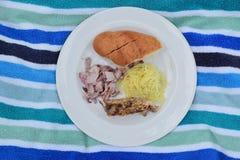 Un pasto tipico di picnic è servito su un asciugamano di spiaggia che mostra il divertimento ed il buon tempo Immagine Stock