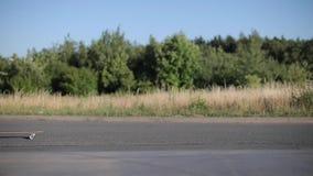 Un patín largo monta a lo largo del camino almacen de video