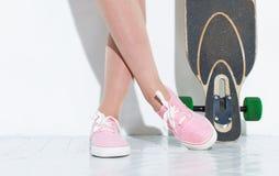 Un patin et des espadrilles roses se ferment vers le haut du mur blanc proche sur un plancher blanc Photo libre de droits