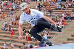 Un patinador profesional en el patinaje en línea salta la competencia en los juegos extremos de Barcelona de los deportes de LKXA Foto de archivo libre de regalías