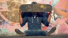 Un patinador sonriente está torciendo a su tablero mientras que se sienta al lado de una pared de la pintada almacen de video