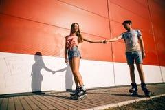 Un patinage à roulettes de couples au coucher du soleil Photographie stock