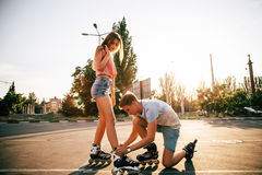 Un patinage à roulettes de couples au coucher du soleil Image stock