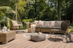 Un patio del rattan ha messo compreso un sofà, una tavola e una sedia su un wo immagini stock libere da diritti