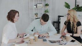 Un patron femelle ambitieux et attrayant agit l'un sur l'autre avec deux dessinateurs d'intérieurs dans l'immeuble de bureaux mod banque de vidéos