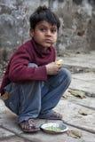 Un pauvre garçon semblant mangeant par le côté de route à la Nouvelle Delhi Photos libres de droits