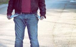 Un pauvre homme sans emploi, avec beaucoup de factures pour payer montrer ses poches vides photo stock