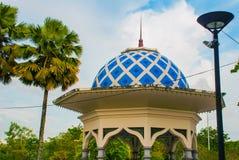 Un pavillon avec un toit bleu et des palmiers sur le fond de ciel Miri City Fan Park, Bornéo, Sarawak, Malaisie Photographie stock libre de droits
