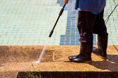 Un pavimento di pulizia dell'uomo con il getto di acqua ad alta pressione Immagini Stock