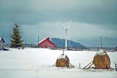 Un paysage d'hiver en montagnes avec la girouette et une maison Photos stock