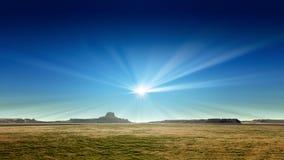 Un paysage de désert avec le soleil rayonne dans le ciel bleu Images stock