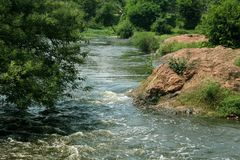 Un paysage de petite rivière avec des roches et des arbres Image libre de droits