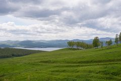Un paysage nuageux de ressort avec une colline de floraison et un lac dans la distance photographie stock libre de droits
