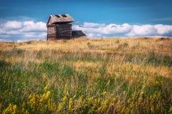 Un paysage rural avec une structure à deux étages abandonnée de rondin avec un toit de vol Mettez en place avec les herbes et le  Photographie stock libre de droits