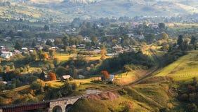 Un paysage rural de bel automne avec une vallée ensoleillée, de petites maisons, un vieux viaduc et un chemin de fer d'enroulemen Photos libres de droits