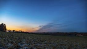 Un paysage a tiré d'un champ juste après le coucher du soleil Images stock