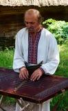 Un paysan ukrainien joue le Tsymbaly Photographie stock libre de droits