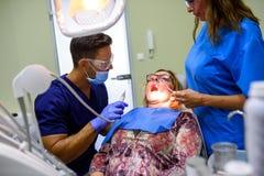 Un paziente che ottiene assistito e trattamento in uno studio dentario Fotografia Stock Libera da Diritti