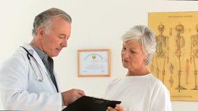Un paziente che risponde al suo medico circa alcune domande video d archivio