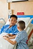 Un paziente e un figlio con il dispositivo di venipunzione salino (iv) Immagine Stock