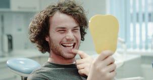 Un paziente molto felice nella stanza del dentista che esamina i suoi denti da uno specchio e che controlla i risultati di un'imb archivi video