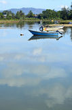 Un pêcheur non reconnu dans un bateau de pêche en bois isolé sur le C.A. Images stock