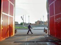 Un peatón cruza delante de la puerta anaranjada grande fotografía de archivo libre de regalías