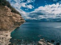 Un pedazo acodado de roca que resalta sobre el mar fotos de archivo