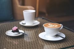 Un pedazo de bocado y de dos tazas del café con leche en la tabla Fotografía de archivo libre de regalías