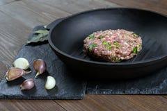 Un pedazo de carne picadita cruda con las hierbas y de ajo en una cacerola de la parrilla del arrabio miente en una piedra gris Imágenes de archivo libres de regalías