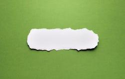 Un pedazo de documento rasgado sobre un fondo verde Foto de archivo libre de regalías