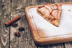 Un pedazo de empanada de manzana cortada con canela en textura de madera del fondo del vintage Fotos de archivo libres de regalías