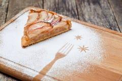 Un pedazo de empanada de manzana cortada con canela en textura de madera del fondo del vintage Foto de archivo libre de regalías