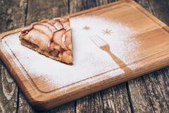 Un pedazo de empanada de manzana cortada con canela en textura de madera del fondo del vintage Imagenes de archivo