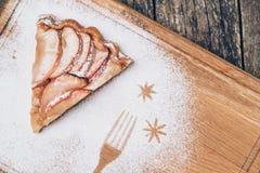 Un pedazo de empanada de manzana cortada con canela en textura de madera del fondo del vintage Visión superior Imagen de archivo libre de regalías