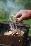 Un pedazo de madera de los controles de la mano del varón bajo comienzo de la inflamación un fuego del campo Fotos de archivo libres de regalías