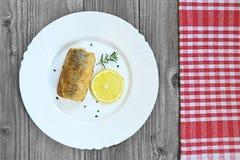 Un pedazo de merluza frita pesca en la placa Fotos de archivo libres de regalías