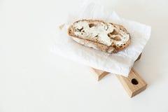 Un pedazo de pan con mantequilla y sal miente en un tablero de madera en un fondo blanco Imagen de archivo libre de regalías