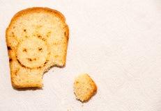 Un pedazo de pan de la tostada en una toalla de papel con el sol sonriente Fotografía de archivo