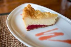 Un pedazo de pastel de queso de la fresa con la salsa de la fresa fotos de archivo libres de regalías
