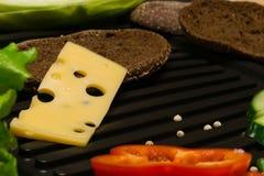 Un pedazo de queso con los agujeros Imágenes de archivo libres de regalías