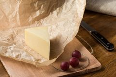 Un pedazo de queso duro envuelto en documento y uvas rojas sobre la tabla de cocina fotos de archivo
