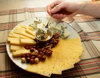Un pedazo de queso en una bifurcación en la mano del hombre y corrió abajo con su miel Fotografía de archivo libre de regalías