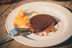 Un pedazo de torta de chocolate con el melocotón en la tabla de madera en el café, primer Fotografía de archivo